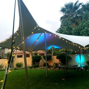 6m x 7.5m stretch tent with fairy lights and blue parcan lights in a garden